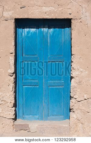 Blue door at wall in remote village at Altiplano, Bolivia, South America