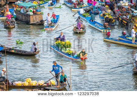 Soc Trang, Vietnam - February 3rd, 2016: The couple sold daisies boatman, watermelon, many boats around the busiest crossing in the morning floating market on the river in the countryside in Soc Trang, Vietnam
