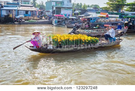 Can Tho, Vietnam - February 4th, 2016: Couple rowing boats sold chrysanthemum New Year display on floating market with full yellow flowers beautiful morning end of year as a way earning living river in Can Tho , Vietnam.