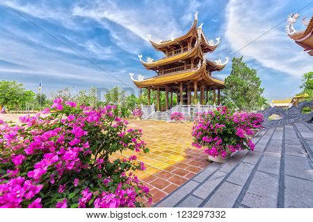 Can Tho, Vietnam - February 4th, 2016: Architecture temples with high-rise towers, next to the flower pots, lined paper and yard Bat Trang bricks express cultural beauty in Can Tho, Vietnam