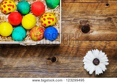 Easter eggs in a nest of straw on the old wooden background
