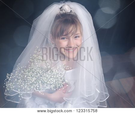 Very young bride. Wedding white dress. Luxury veil. Happy smile. Portrait of a child bride