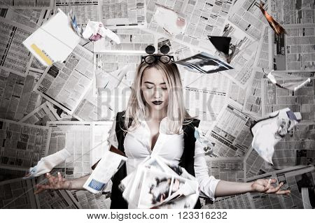Young blonde in a sunglasses surrounded with newspapers