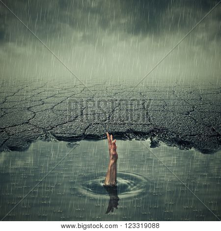 Surrealistic image with a single hand of drowning man asking for help in a pothole of cracked asphalt. Broken pavement with a dirty water puddle in a imaginary town.