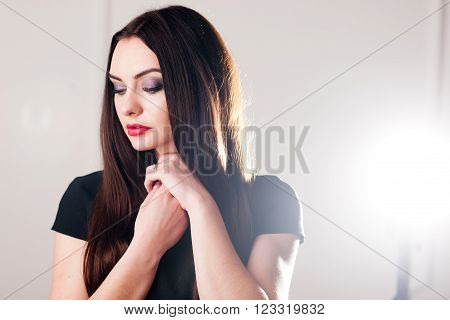 Studio shoot of gentle timid brunette on beige background. Gentle timid girl confused by camera. Young embarrassed girl in black against beige background.