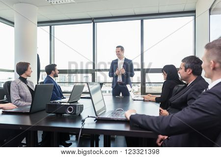 Successful team leader and business owner  leading in-house business meeting, explaining business plans to his employees. Business and entrepreneurship concept.