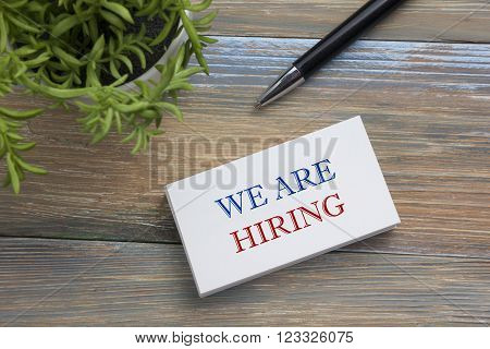 We are Hiring. Office desk table with business card, pen and flower. Top view