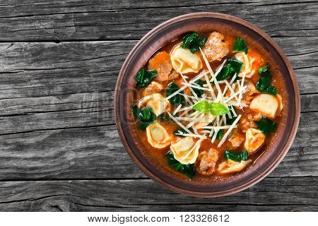 tortellini soup with italian sausages spinach tomato parmesan cheese top-view