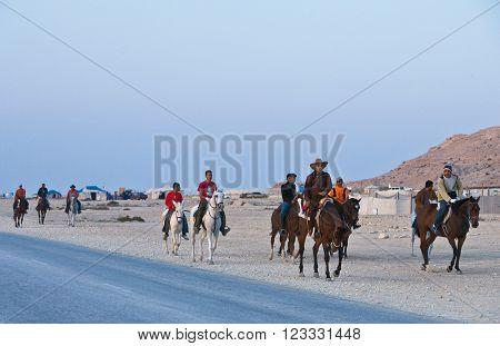 Sakhir,  Bahrain - January 12, 2007:  Local people on horses spending the week-end in the desert.