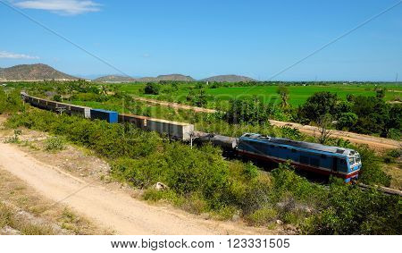 BINH THUAN, VIET NAM- FEB 1, 2016: Train moving on rail to transport passenger and good cross Binh Thuan, Viet Nam, green landscape at Binhthuan, Vietnam rural on day rural on day