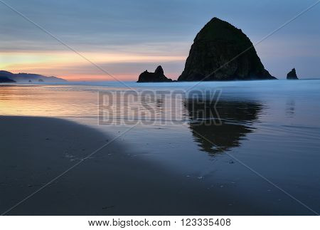Cannon Beach, Haystack Rock Dawn, Oregon, USA. Sunrise at Haystack Rock in Cannon Beach, Oregon as the surf washes up onto the beach. United States.