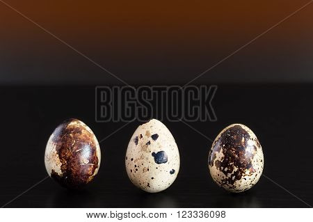 Three upright quail eggs on a black wooden table with orange gradient background
