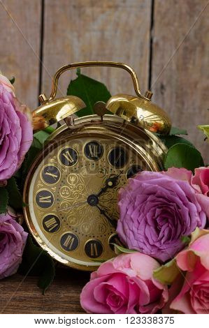 bouquet of pink and violet  fresh roses with vintage alarm clock.