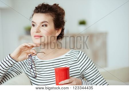 There is no place like home. Beautiful young woman is relaxing and smiling. She is drinking hot beverage and sitting on sofa. The lady is holding eyeglasses