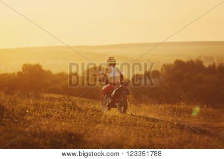 Woman biker rides in fields. Sporty woman biker at motobike. Countryside, country road.  sunset, female motorcycle rider, motorbike rider travel the world, girl resting, freedom lifestyle, back view poster