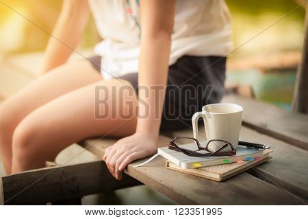 Notebooks pen glasses and coffee cup are putting down on the wood waterside while young woman sitting beside them in weekend with morning scene