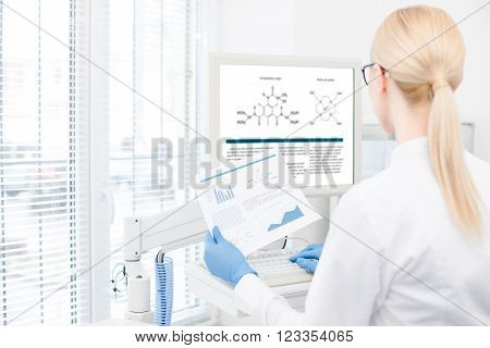 Professional female scientist is comparing results of her research with medical graphic on the computer. She is standing and looking at the monitor with concentration. Focus on her back