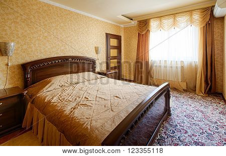 Vintage classic hotel bedroom interior. Bedroom interior design. Vintage bedroom, elegant and luxurious. Hotel premium luxurious classic interior. Double bed with golden bedcover.