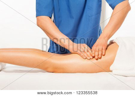 Close-up photo of masseur's hands kneading female hip on the massage couch