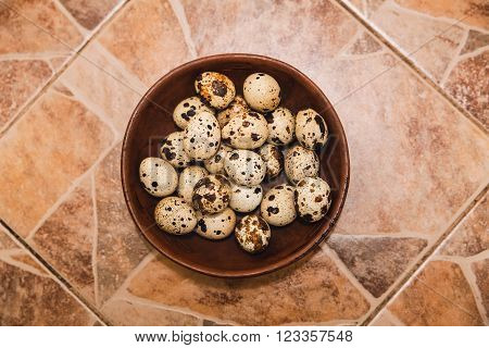 quail eggs are in the clay plate on tiled floor