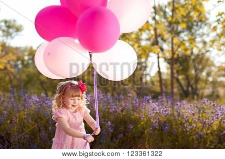 Smiling child girl 3-4 year old with pink balloons outdoors. Birthday party. Playful. Childhood. Little princess.
