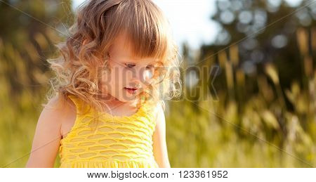 Kid girl 4-5 year old walking in meadow. Wearing casual yellow dress. Looking down. Childhood.