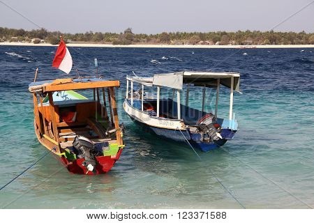 View of wooden boats and blue sea in tropical Gili islands. Travel paradise place.