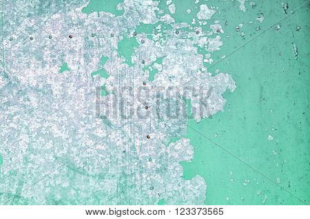 Textured industrial grunge background - pale green chipped paint with silver streaks of paint on the old rough metal surface