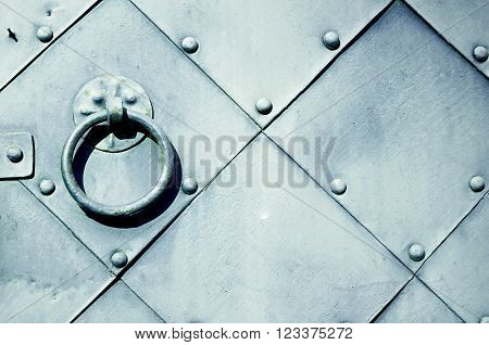 Old grey door with rivets and aged metal door handle in the form of ring. Textured vintage background.