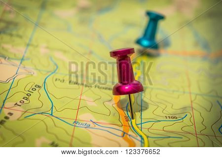 Two pushpins pink and blue embedded in the green map with yellow road