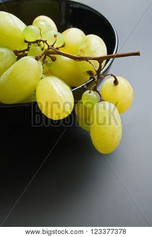 Fresh ripe bunch of grapes placed in black ceramic bowl close up on neutral gradient background
