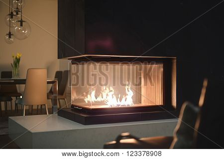 Close-up view of glass fireplace with burning fire inside and a black chimney. On the background there is a table with flowers in vases, chairs and glass round lamps over them. In front of fireplace there is a dark armchair.