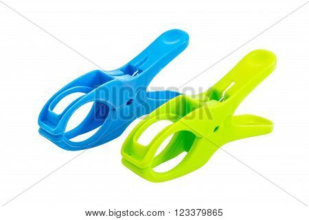 Closeup of two plastic spring clamps (Blue, Green) isolated over white background.