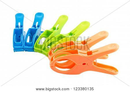 Closeup of three plastic spring clamps (Blue, Green, Orange) isolated over white background.