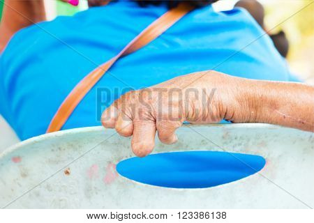 closeup hand of old man suffering from leprosy on the backrest of plastic chair.