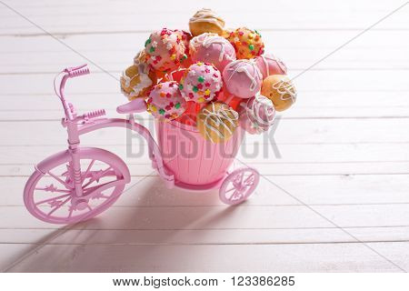 Cake pops in decorative pink bicycle on white wooden background. Selective focus.