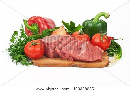 Fresh raw beef meat slices over wooden board with vegetables on a white background