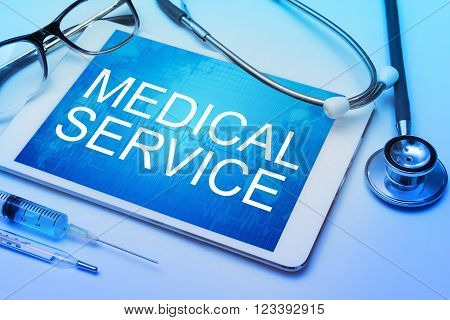 Medical Service word on tablet screen with medical equipment on background