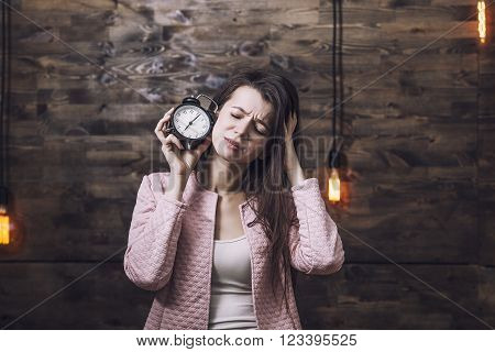 Beautiful young smart woman with alarm clock in hand and a sour face to indicate the concept of time constraints