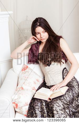 Young brunette woman sitting on couch with open book