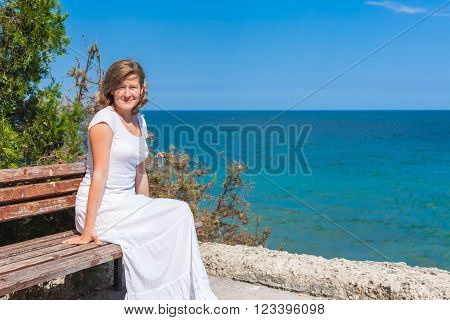 Young woman wearing white sitting on old bench with view of  blue sea on a bright summer day