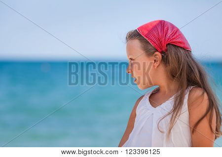 Little girl looking ahead against sea background