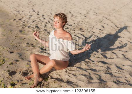 Beautiful woman sitting on beach and meditating in lotus position