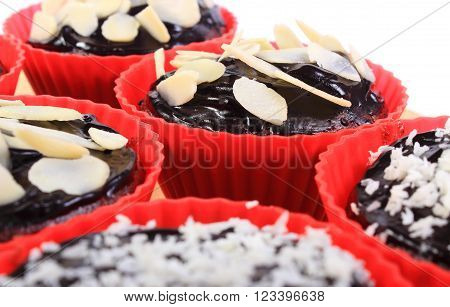 Homemade delicious fresh baked chocolate muffins with desiccated coconut and sliced almonds in red silicone cups, concept for dessert