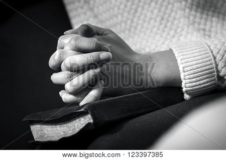 Christian woman pray and folds hands over the Holy Bible.