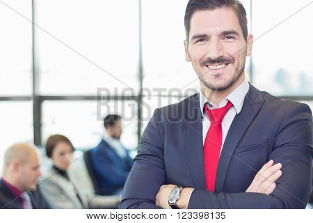 Successful team leader and business owner proudly standing with crossed arms with  coworkers working in office in background. Business and entrepreneurship concept.