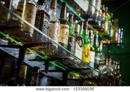 Bucharest Romania - March 26 2016: Several types of bottled alcohol are displayed on some shelves in a pub in Bucharest Romania.