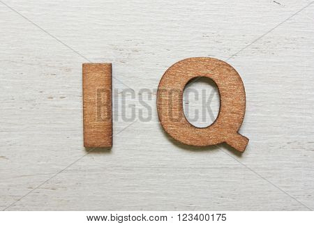 Word IQ (intelligence quotient) are made with wooden letters on an old white wooden background