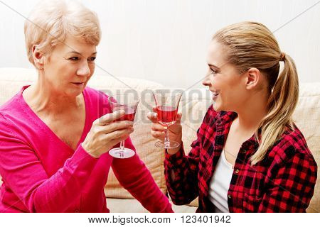 Happy senior woman with daughter or grandaughter drinking wine