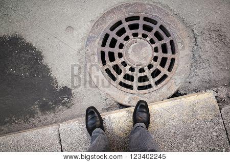 Urbanite Man Stands Near Rusty Sewer Manhole